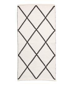 Hvid/Sortmønstret. Bomuldsgulvtæppe med jacquardvævet mønster.