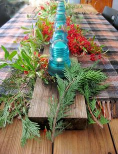 Down the center of the redwood table over a plaid blanket, I placed an old barn board to hold the insulators, each with a small light inside from a string of battery powered lights not used last month. The light string has 16 lights and I placed the insulators over every other one. The cedar branches and the berries were arranged between and this color pleases me next to the lit aqua glass.  Simple and refreshing!