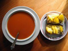 Tomatsuppe og grove rundstykker med smør og gul paprika.