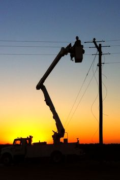 Beautiful shot of a lineman working at sunrise.