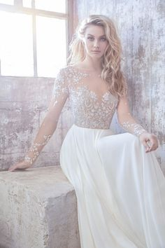 Ivory chiffon A-line bridal gown, long sleeve illusion bodice with metallic floral micro beading, bateau illusion neckline and fully beaded back.