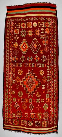 Africa | Floor rug from the Moroccan Arab/Berber, Oulad Bou Sbaa tribe living on the Marrakesh Plains | ca. mid 20th century | Wool and goat hair; knotted pile, weft-faced. | The Oulad Bou Sbaa tribal weavers were significantly influenced by commercially successful urban carpet production. Weavers frequently incorporated Rabat carpet motifs, which originated in Turkish rugs imported during the period of Ottoman political influence.