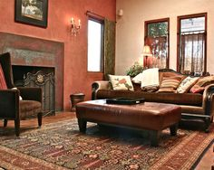 Terracotta wall color with texture is great, blending beautifully with the oriental rug, leather ottoman and copper colored patina on the metal fireplace surround.