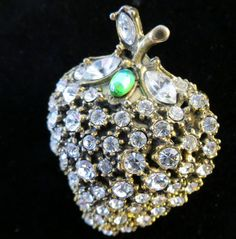 This is a gorgeous rhinestone vintage brooch designed and signed by ART.  It is in the shape of a strawberry, covered in rhinestones with gradually larger stones from bottom to top. It has on green stone at the top.
