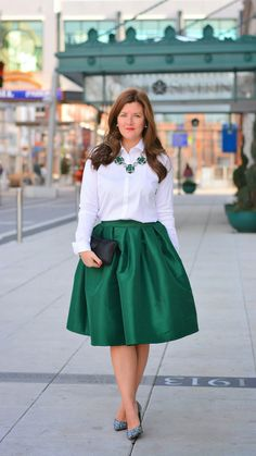 A full A-line skirt in metallic emerald green. In stiff fabric that holds it shape. Details: - 100% Polyester - Lined - Machine wash Coverage Information: Length- At the knee length, 22' which will co