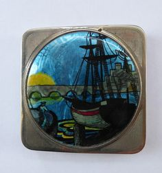 This is a highly collectable little 1930s powder compact called a Stratnoid - which was made by the famous Stratton Company. The compact is of miniature size - designed to fit into a tiny evening bag of a flapper. It is 2 inches square. The compact is made of chrome - and a special rotating non spill cover mechanism inside. The top of the compact shows a Deco design showing a sailing ship at anchor - with a bridge in the distane and a large yellow setting sun. This image is made from foil…