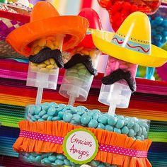 Fill with different colors of chocolate drops or mini gumballs, then pop on a mini sombrero and black mustache. Place in a clear container with candy in a coordinating color and a favor label on the front letting your amigos know to grab one when its time to say adiós.