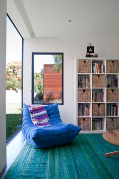 Dwell on Design Exclusive House Tour: Secret House Photo: I love this chair and the alternating baskets in the bookcase