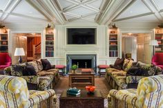 Bookshelves on either side with fine wood detailing accentuate this living room fireplace.
