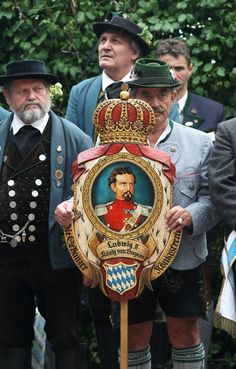 """""""A man wearing a traditional Bavarian costume holds asign showing King Ludwig II…"""