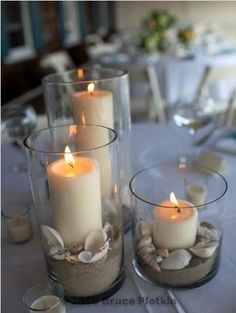 Beach wedding centerpiece with sand and candles (I would skip the shells) by flickr user azaleafloraldesign