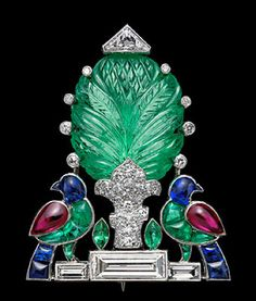 Platinum millegrain brooch centred on a carved emerald representing a tree on a pave set diamond trunk, with eight small diamonds in single collets between the leaves and a triangular cut diamond at the top. Two birds, with sapphire heads and tails, emerald legs and bodies and ruby wings, their heads turned backwards flank the tree, beside navette shaped emerald plants, all resting on a triple baguette cut diamond base. Cartier, London, c. 1935