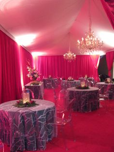 White tent with liner, clear Maria Theresa chandeliers, pink pipe and drape and carpet, sheer white enchanted overlay linens, crystal cylinder centerpieces and clear mirage chairs.