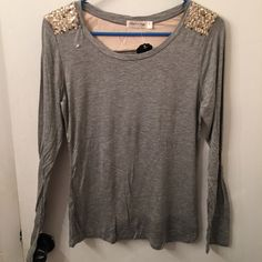 Heather Grey sequin tee Perfect tee for upcoming holiday season. Can dress it up or down. ⭐️⭐️⭐️⭐️I do not trade. Please feel free to make a reasonable offer and we can go from there. I love to bundle and the more items you have the more discount I will give. All sales final. Any questions please feel free to ask!!⭐️⭐️⭐️⭐️ Tops