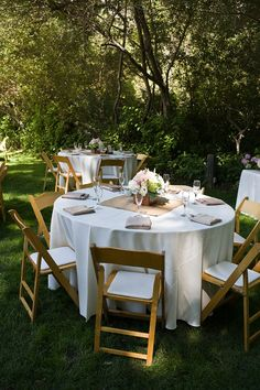 "Round table with white tablecloth and a square, brown/gold ""runner."" Round centerpiece flowers."