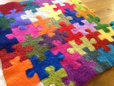 A blanket designed with individually-knit puzzle pieces. Pattern includes center pieces, edge pieces, corners, layout and seaming tips.