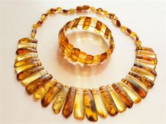 This elegant and eye-catching set consists of natural Baltic Amber cabochons of most common yellow and warm honey colors. The central cabochons are regular shaped and about 2-4 сm long and 8-12 mm width. Central part of necklace with regular shaped cabochons has 21 cm length.   The bracelet has 24 pcs. 15-25 mm cabochons perfectly matched by size.   The cabochons shows some inclusions due to the genuine Amber nature, please see photos to have your own impression.   Tested 100% natural raw…