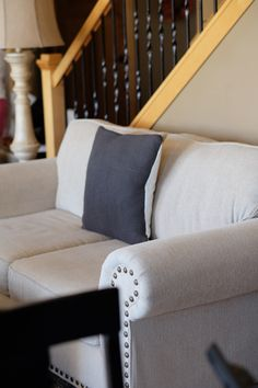 Cozy grey knit sweater pillow against a neutral couch.