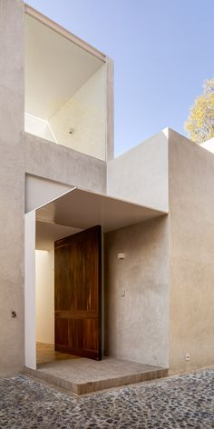 This natural wood pivot door pops against the concrete exterior of this modern house in Mexico. Find the perfect door to compliment your modern project at https://pivotdoorcompany.com/Exterior-Doors/.