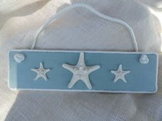 Cute coastal wall plaque, wooden plaque painted blue green with 3 starfish mounted and surrounded by white rope. Ready to hang in your beach cottage or any coastal themed room. The dimensions are 4 x 14 1/2 inches. Custom request welcomed. This is a made to order item. Your item will be similar to the one pictured.