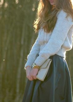 Full skirt and cropped sweater and oversized clutch.