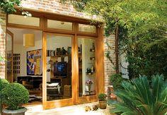 As portas-janela de vidro trouxeram luminosidade para o estar, deixando à mostra o jardim. A caixilharia de madeira foi executada por um marceneiro
