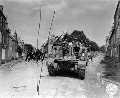 """Coutances, Rue de la Croix Quillard, 28 juillet 1944: une colonne du 66th Armored Field Artillery Bn de la 4th Armored. Div.(arrivant de la route de Saint-Lô). Au premier plan un HMC M-7 Priest de la B Btry. A gauche caviardé un char léger M5A1 Stuart du 25th Cavalry Reconnaissance Squadron (Mechanized), de la 4th Armored Div. arrivant de Périers, a sauté sur une mine et a déchenillé. Un panneau blanc placé à l'entrée de la rue, porte la mention """"MINES"""" pour en interdire la circulation."""