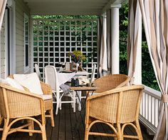 The Perfect Porch...Enhance the columns on a front porch with fabric panels. The tan stripes on the curtains coordinate with the light brown wicker furniture. Dividing the porch into a seating area and a dining area further creates the feel of an outdoor living space.
