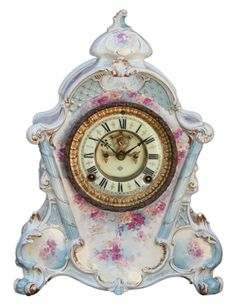 Antique Royal Bonn Porcelain Mantle Clock made by Ansonia Clock Co. in about 1895. It has a nice creamy colored case with light blue accents and pretty pink flowers, and an eight-day movement that strikes on a gong.