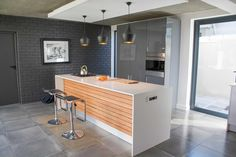 Kitchen Island, ceaser stone unit, Smeg Linear accessories. Ply panelled Island front. Bulk head with Todd Dixon style lighting coupled with shadow lights plus shuttered cement ceiling. Exposed brick painted in aniseed.   #contemporaryinterior #modern residentialarchitecture #capetownhomes #contemporarydesign