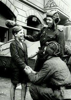 Soviet tankers interacting with a German boy. Berlin, Germany 1945