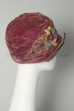 1925 / American / Cloche hat / Red-violet velvet, sectional crown, draped sides, very narrow upturned brim edged with silver braid, with crossover points on R side, sides decorated with 3 clusters of grosgrain ribbon flowers & silk floss embroidery in French knots & brokenlines,