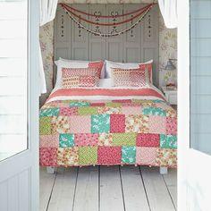 un plancher en bois blanc et un lit à couvre lit patchwork doux