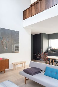 A walnut balustrade sits above the open-plan living space on the mezzanine level which leads to an outdoor terrace.