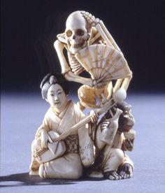 Netsuke. Skeleton with fan behind woman playing samisen, and monkey drinking sake. Ivory. (via British Museum)