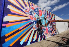 Community artists have come together to paint a mural on a wall in downtown New Philadelphia that was once covered in debris and graffiti.