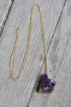 This beautiful necklace features a long gold tone chain with a raw amethyst druzy crystal charm. The crystal has gold trim lining the edges and attaching it to the chain. Each necklace is one of a kind, so crystal size or clarity may vary slightly. This necklace was handmade by Sadie Designs.