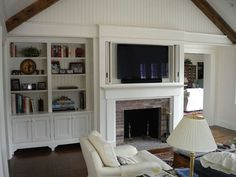 Traditional pocket doors in a built-in fireplace surround house a flat screen TV