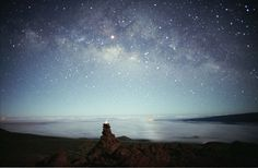 """The Milky Way's cosmic clouds of stars and dust stretch across this picture taken May 2001 from Hawaii. In the foreground is an """"ahu hoku"""" - a star marker or star altar - built up of rocks topped with a white piece of coral glowing in the moonlight. Photo by Barney Magrath"""
