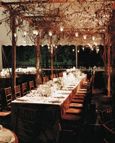 Votive candles illuminated a canopy of grapevine arbor at this formal wedding in…