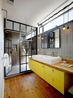 bathroom with yellow floating vanity, wood floors, and an industrial-style shower