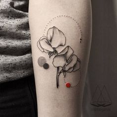 Graphic sweet pea tattoo on the left forearm.