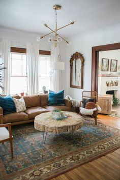 Emily Netz: Our 1920 Sears Kit House Before & After Tour // Part 1 bohemian retro mid century modern design style for 1920s home. Living room with leather couch, windows, wood mirror, wood log shaped coffee table, blue patterned rug