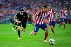 David Villa of Club Atletico de Madrid is marshalled by Marc Bartra of Barcelona during the UEFA Champions League Quarter Final second leg match between Club Atletico de Madrid and FC Barcelona at Vicente Calderon Stadium on April 9, 2014 in Madrid, Spain.