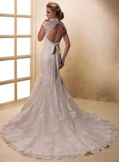 Romantic and feminine in its display of tulle and lace, this fit and flare gown with corded lace illusion sleeves, V-neckline and keyhole back features Swarovski crystals sprinkled on scattered motifs and detachable beaded grosgrain ribbon belt. Finished with covered button over zipper closure.