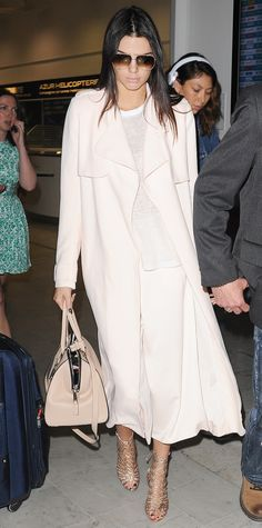 Kendall Jenner landed at Nice airport in the sweetest ensemble—she paired her blush Camilla and Marc culottes with a matching trench and styled the one-color combo with a pale top, a nude tote, and gold Sophia Webster lace-up cage booties.