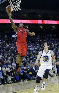 Toronto Raptors' Kyle Lowry (7) scores past Golden State Warriors' Nemanja Nedovic (8) during the first half of an NBA basketball game on Tu...