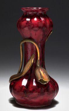 Zsolnay In der Art einer stilisierten, gerippten Kürbisfrucht mit passig gewelltem Lippenrand. H. 23,8 cm. Entwurf: Lajos Mack, um 1900. Unterseite bez.: Fünf-Kirchen-Marke ZSOLNAY PÉCS (dunkelroter Schriftzug), 5104/29 03/L1,8eE