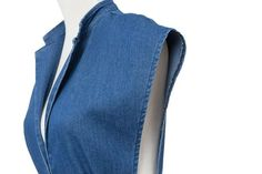The Zoie Dressfeatures a sleevelessdenim dresswith a turn-down collar and a deep plunge neckline. Front slit pockets with a button waistband. Small slit in f