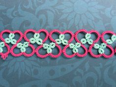 "Nice effect with two colors, tatting  heart pattern, here it is:    R4-4, C6-11, R4+4, C11-6, R4+4 rw R4-4 (here I made the join by wrapping the thread around the thread that is between the two small rings so that there is pink on both sides), C6-11 and so on.  I've not put all the ""RWs"" in there but I think it's pretty well self-explanatory."